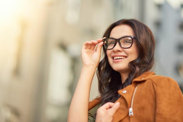 Retrato de uma jovem mulher de negócios alegre ajustando seus óculos e olhando para o lado enquanto