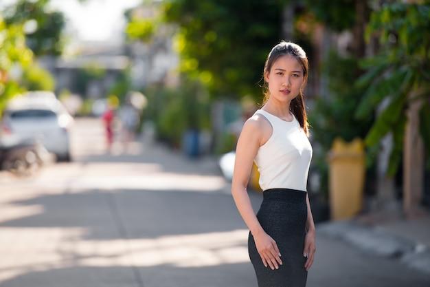 Retrato de uma jovem mulher de negócios asiática bonita na rua ao ar livre