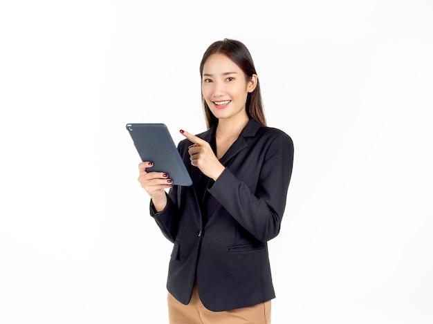 Retrato de uma jovem mulher de negócios asiática de terno preto segurando e apontando o dedo para o tablet