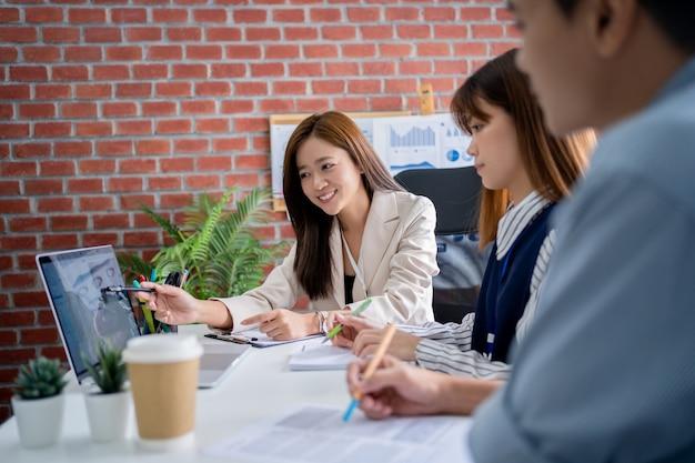 Retrato de uma jovem mulher de negócios asiática explicando seu trabalho em um computador para seus colegas no local de trabalho.