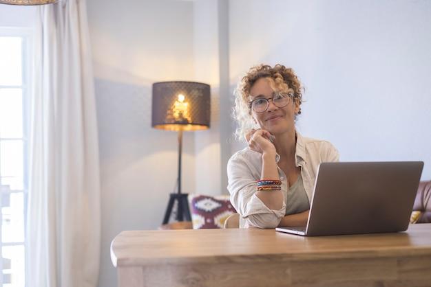 Retrato de uma jovem mulher de negócios atraente e alegre sorrindo e olhando enquanto trabalha