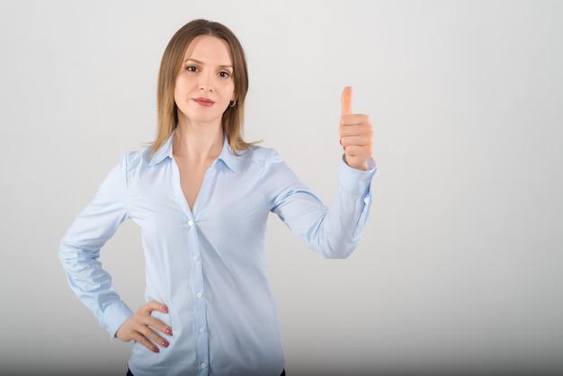 Retrato de uma jovem mulher de negócios atraente mostrando o grande polegar para cima a placa com os dedos sobre fundo branco
