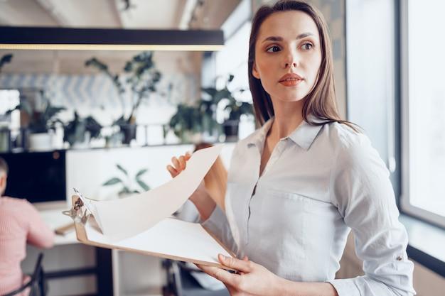 Retrato de uma jovem mulher de negócios atraente segurando uma prancheta no escritório