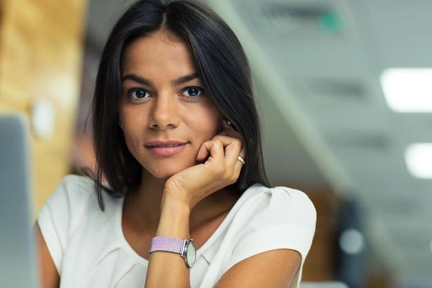 Retrato de uma jovem mulher de negócios bonita no escritório, olhando para a câmera