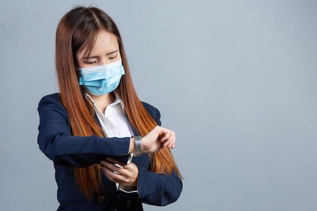 Retrato de uma jovem mulher de negócios bonita usando máscara facial na superfície cinza