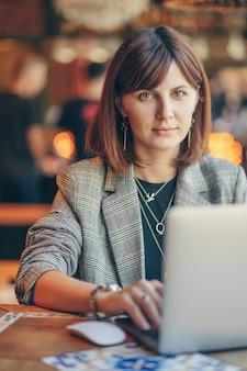 Retrato de uma jovem mulher de negócios com blazer cinza, sentado à mesa no café e trabalhando no netbook. freelancer, trabalhar numa cafetaria.