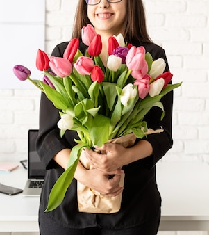 Retrato de uma jovem mulher de negócios confiante em pé ao lado da mesa com um buquê de tulipas frescas