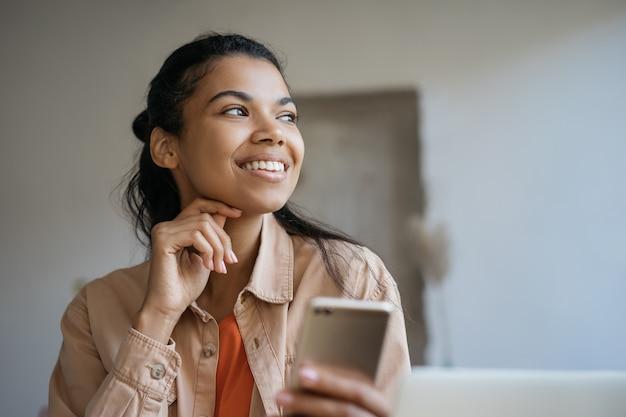 Retrato de uma jovem mulher de negócios confiante usando telefone celular, trabalhando em um escritório moderno