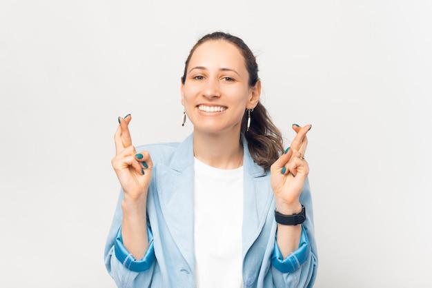 Retrato de uma jovem mulher de negócios cruzando os dedos e desejando o melhor