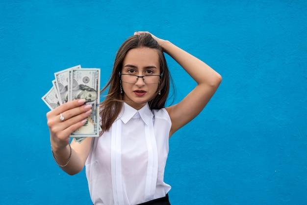 Retrato de uma jovem mulher de negócios de sucesso segurando muitas notas de dólar de dinheiro isoladas em azul Foto Premium
