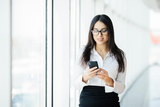 Retrato de uma jovem mulher de negócios digitando telefone de texto contra janelas panorâmicas. conceito de negócios