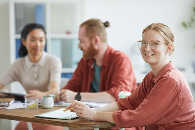 Retrato de uma jovem mulher de negócios em óculos, sorrindo enquanto está sentado à mesa durante uma reunião de negócios no escritório