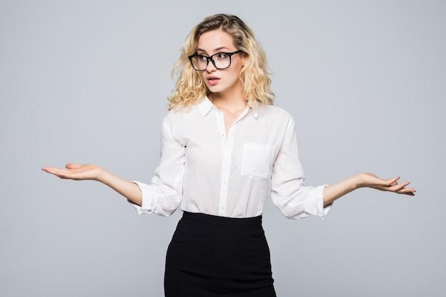Retrato de uma jovem mulher de negócios encolhendo os ombros sobre uma parede cinza