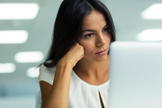 Retrato de uma jovem mulher de negócios linda trabalhando em um laptop no escritório
