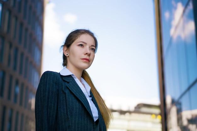 Retrato de uma jovem mulher de negócios na rua perto do centro de escritórios. em uma jaqueta preta e camisa branca