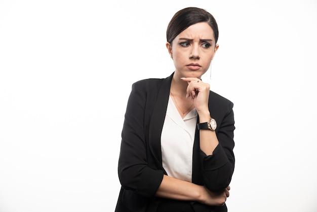 Retrato de uma jovem mulher de negócios posando na parede branca.