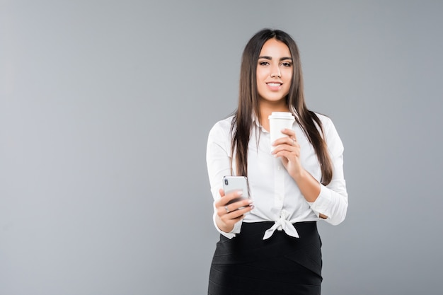 Retrato de uma jovem mulher de negócios satisfeita, usando o telefone celular, segurando uma xícara de café para ir isolado no branco