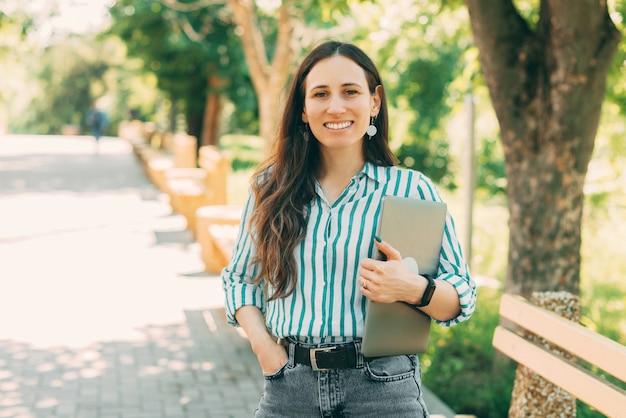 Retrato de uma jovem mulher de negócios segurando um laptop e caminhando no parque durante o verão