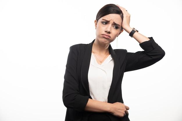Retrato de uma jovem mulher de negócios tocando sua cabeça.
