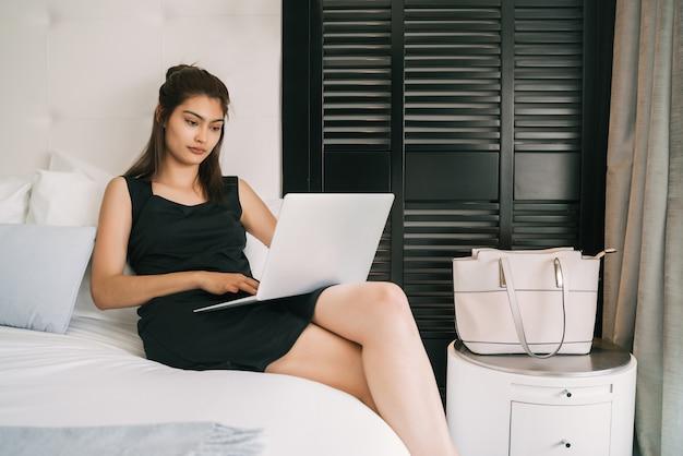 Retrato de uma jovem mulher de negócios trabalhando em seu laptop no quarto do hotel.
