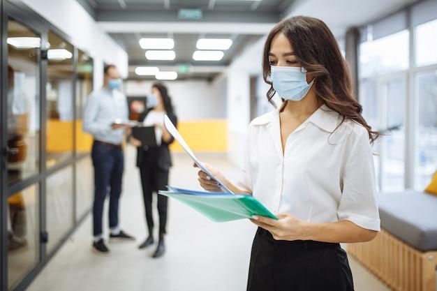 Retrato de uma jovem mulher de negócios usando uma máscara médica, verificando papéis, tendências e perspectivas de negócios em um corredor de escritório.