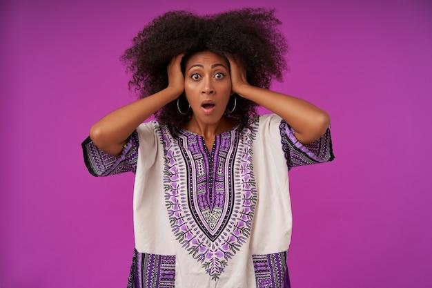 Retrato de uma jovem mulher de pele escura assustada segurando a cabeça com as mãos com medo, posando em roxo em roupas casuais
