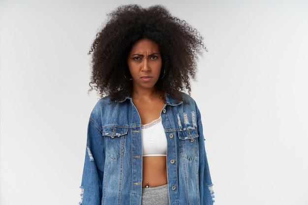 Retrato de uma jovem mulher de pele escura encaracolada com raiva posando sobre uma parede branca com as mãos para baixo, vestindo blusa branca e casaco jeans, com os lábios dobrados e franzindo a testa