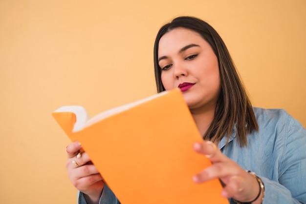 Retrato de uma jovem mulher de tamanho, curtindo o tempo livre e lendo um livro em pé contra a parede amarela.