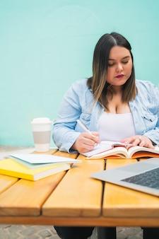 Retrato de uma jovem mulher de tamanho pluse estudando com laptop e livros enquanto está sentado ao ar livre no café.