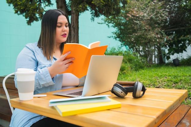 Retrato de uma jovem mulher de tamanho pluse estudando com um laptop e livros enquanto está sentado ao ar livre em uma cafeteria