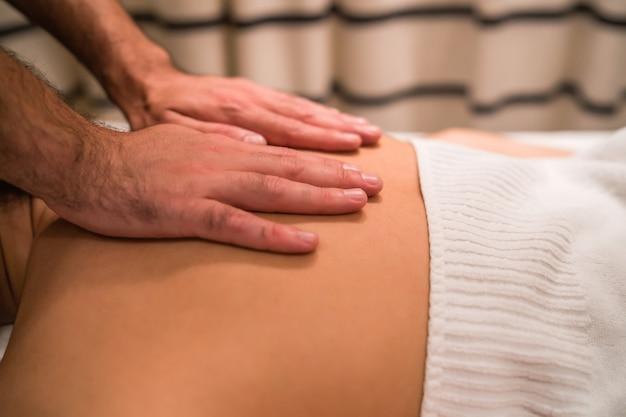 Retrato de uma jovem mulher deitada sobre a mesa de tratamento e recebendo massagem relaxante nas costas no salão spa.