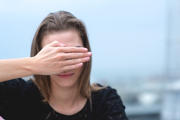 Retrato de uma jovem mulher deprimida com as mãos cobrindo o rosto