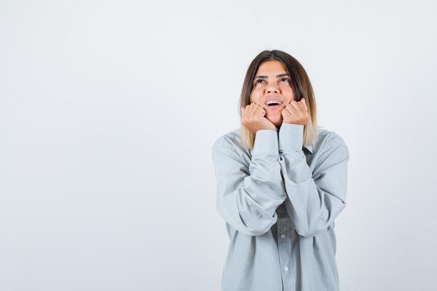 Retrato de uma jovem mulher descansando em suas mãos com uma camisa grande e uma linda vista frontal