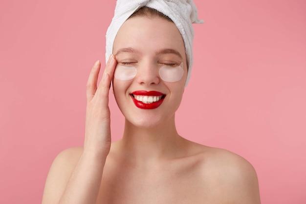 Retrato de uma jovem mulher desfrutando após o banho com uma toalha na cabeça, com manchas e lábios vermelhos, toca o rosto, carrinhos.