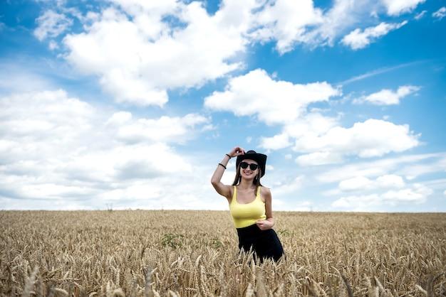 Retrato de uma jovem mulher desportiva no campo de trigo no verão. estilo de vida