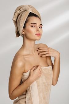 Retrato de uma jovem mulher elegante bonita após o banho que está coberto de toalha.