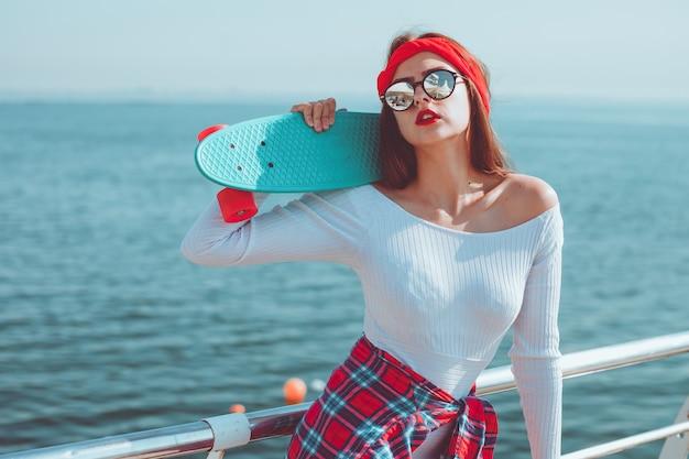 Retrato de uma jovem mulher elegante em roupa elegante com skate nas mãos na praia contra o mar