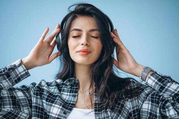 Retrato de uma jovem mulher em fones de ouvido, ouvindo música