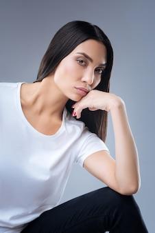 Retrato de uma jovem mulher em uma camiseta branca posando contra uma parede cinza