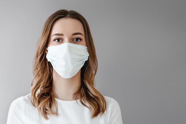 Retrato de uma jovem mulher em uma máscara médica isolada sobre fundo cinza. paciente jovem fica contra o fundo da parede, copie o espaço para texto