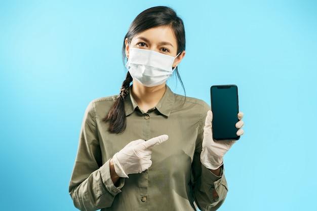 Retrato de uma jovem mulher em uma máscara médica protetora e luvas apontando para a tela de um smartphone em um fundo azul. copie o espaço