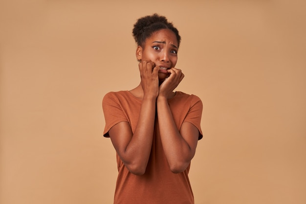 Retrato de uma jovem mulher encaracolada de pele escura e olhos saltados levantando as mãos assustadas para o rosto e fazendo uma careta enquanto olha assustadoramente, isolado em bege