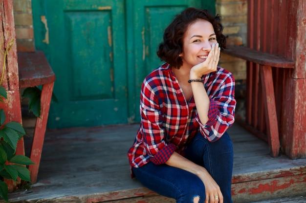Retrato de uma jovem mulher encaracolado perto da casa velha ao ar livre em dia de sol. menina sorridente e emocional em jeans e camisa vermelha na rua da cidade.