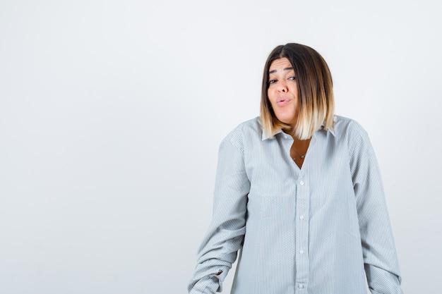 Retrato de uma jovem mulher encolhendo os ombros enquanto posa com uma camisa grande e uma vista frontal sem noção