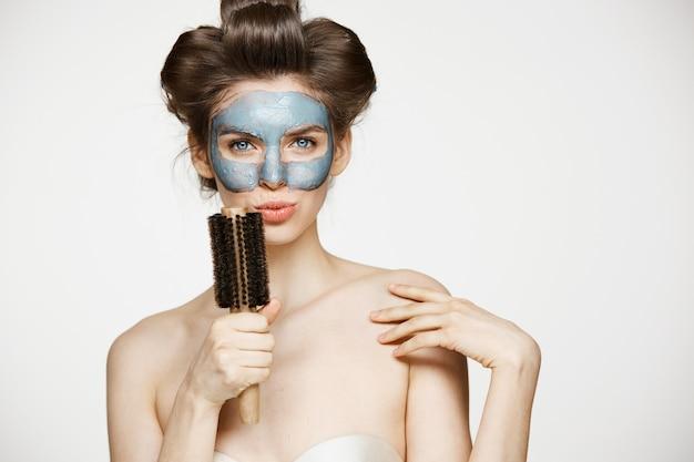 Retrato de uma jovem mulher engraçada em rolos de cabelo e máscara facial cantando no pente. conceito de beleza e cuidados de pele.