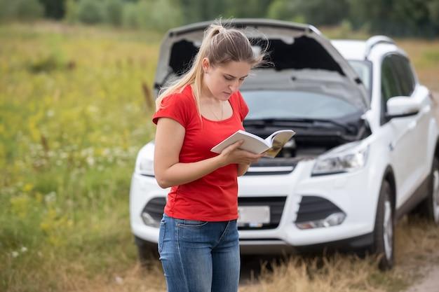 Retrato de uma jovem mulher estressada diante de um carro quebrado e lendo o manual do proprietário