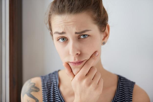 Retrato de uma jovem mulher europeia tatuada, mostrando suspeita com sobrancelhas escuras franzidas. linda menina morena em top despojado, segurando seu queixo com o polegar e o dedo indicador, ficando em dúvida.