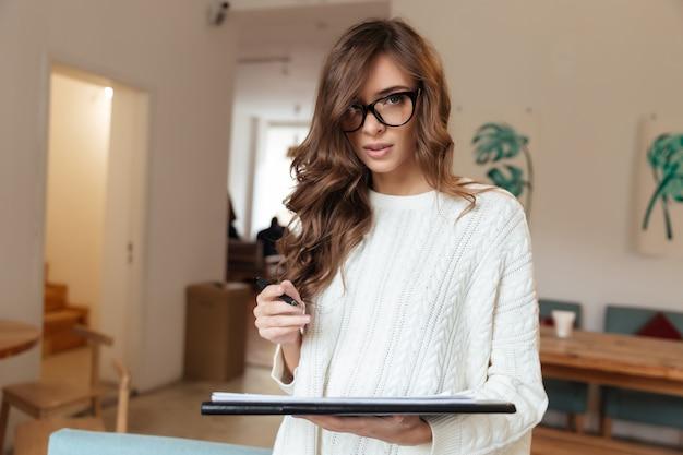 Retrato de uma jovem mulher fazendo anotações
