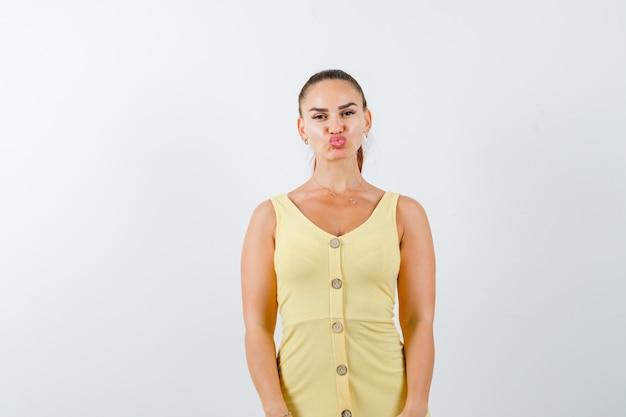 Retrato de uma jovem mulher fazendo beicinho com um vestido amarelo e uma linda vista frontal