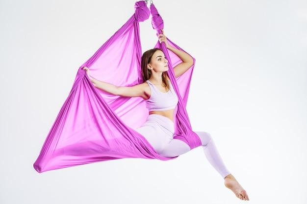Retrato de uma jovem mulher fazendo yoga anti-gravidade. o conceito de harmonia e tranquilidade